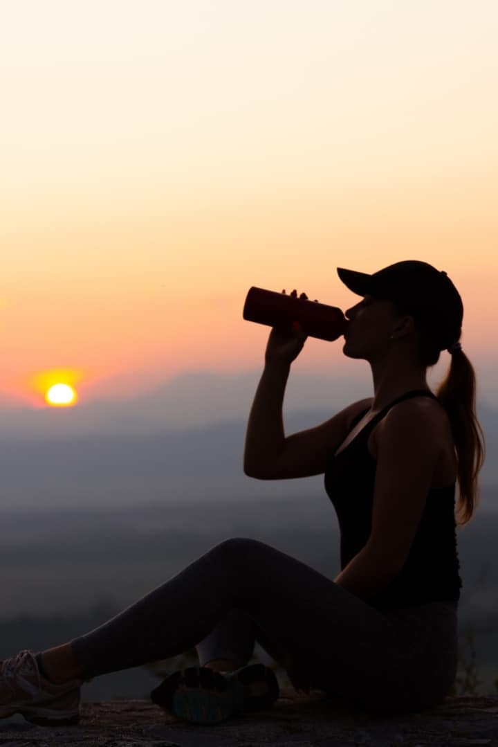 Side view image of a woman wearing a ball cap, drinking out of a water bottle, and she is sitting on the ground in front of a sunset.