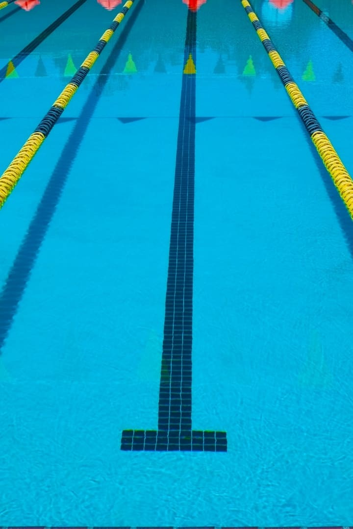Close up view of the length of a pool, showing the guide line and the ropes to separate the lanes.
