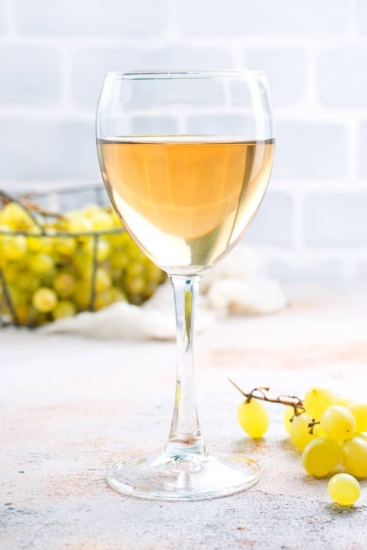 Side view of a glass of white wine, with grapes beside the wine and a basket of grapes behind the wine.