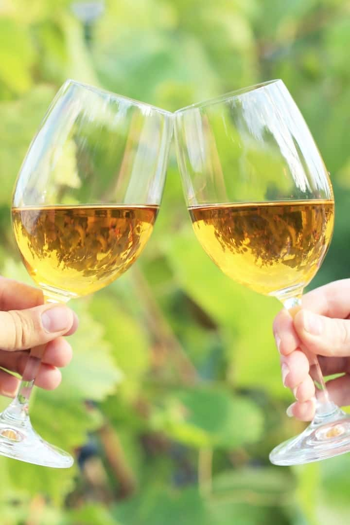 Close up image of two hands holding glasses of white wine, with the glasses being touched together in a cheers motion.