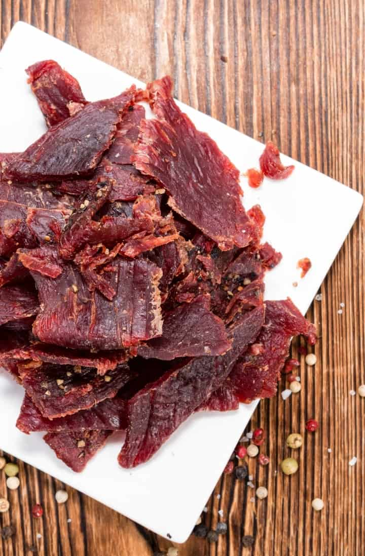 Overhead view of prepared beef jerky, piled on a square white cutting board, with spices surrounding it.