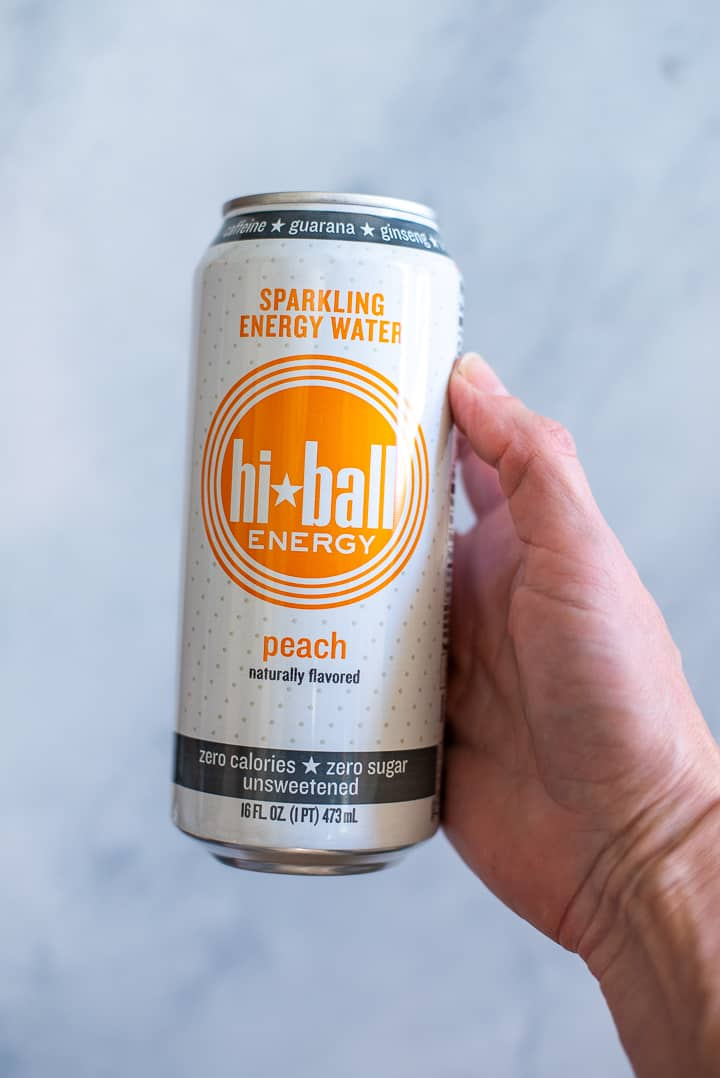 Close up side view of a hand holding an energy drink called Hi-Ball, which is in a white and orange can.