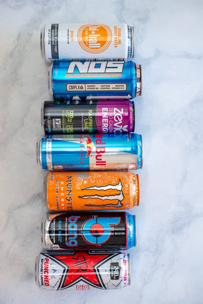 Image of 7 cans of energy drinks lined up on a marble countertop, lying down.