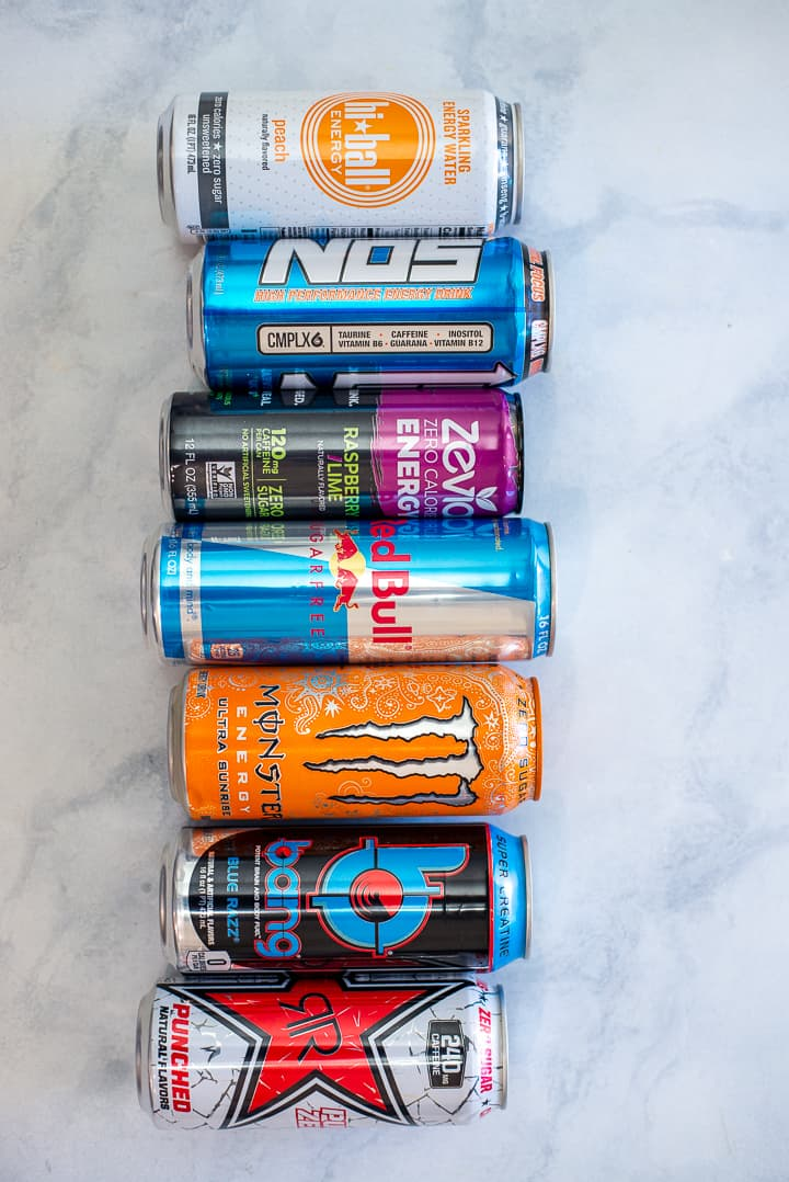 Overhead image of 7 colorful cans of energy drinks like Bang, Monster, and Zevia, lined up lying down on the counter.