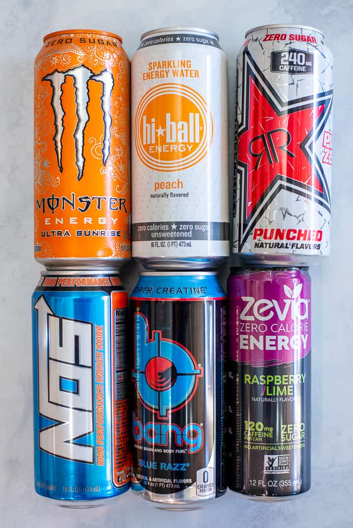 Close up image of 6 cans of energy drink, including Monster, Hi-Ball, RR, No5, Bang, and Zevia stacked on the counter.