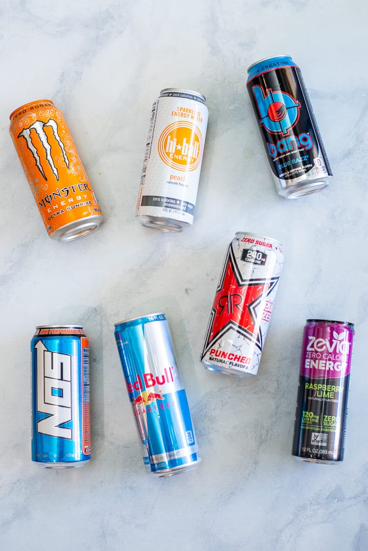 Close up image of 7 colorful cans of energy drinks like Red Bull and Hi-Ball, laying down on the counter.