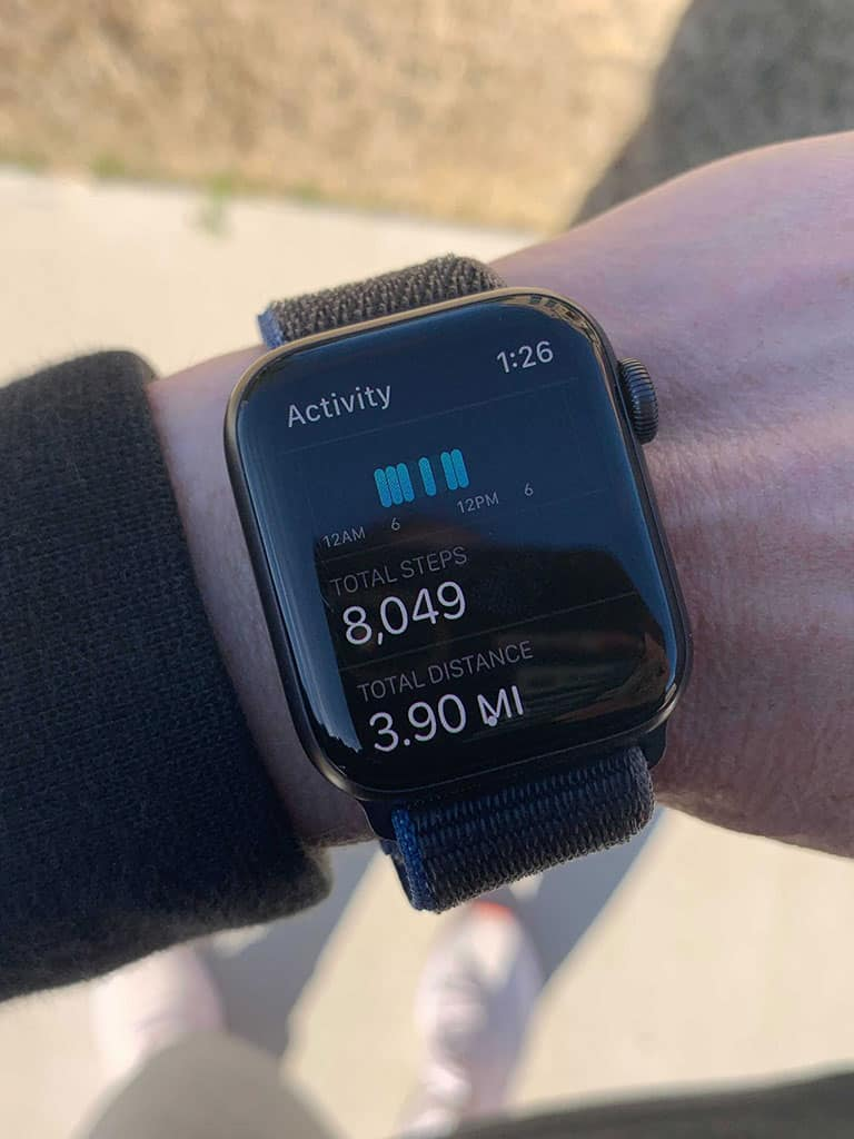 Demonstrating how many steps to lose weight, a close up view of an arm displaying an Apple watch showing the steps taken to be 8049 and the miles logged 3.90.
