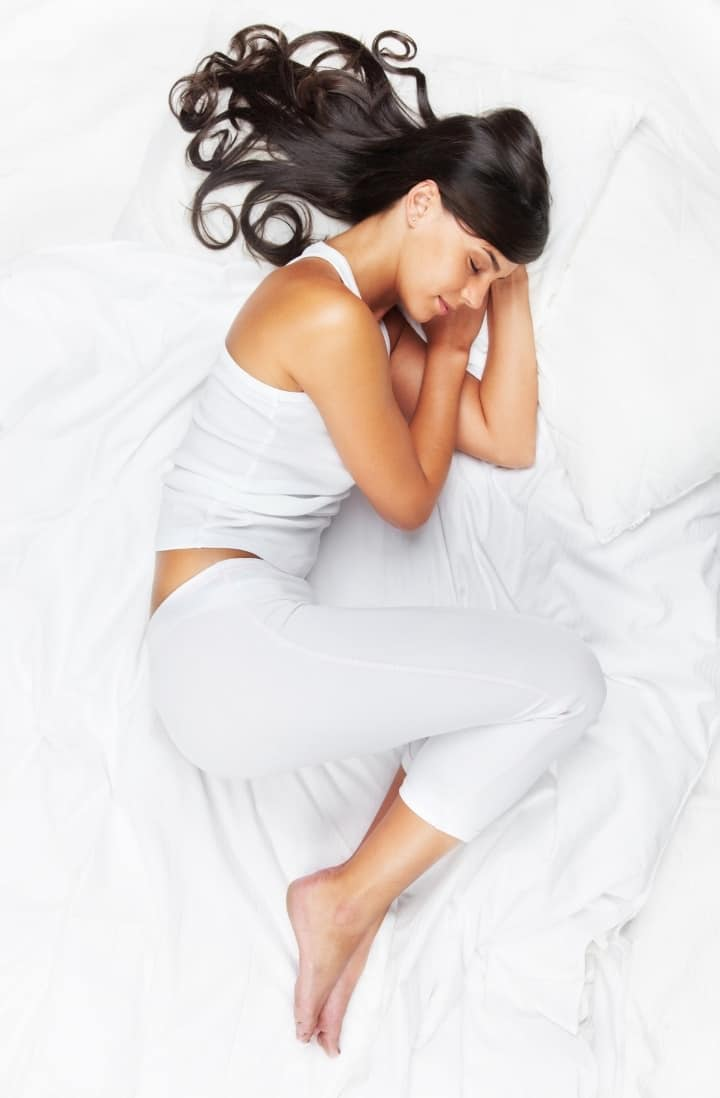 Overhead image of a woman dressed in white pajamas, sleeping on her side in a white bed.