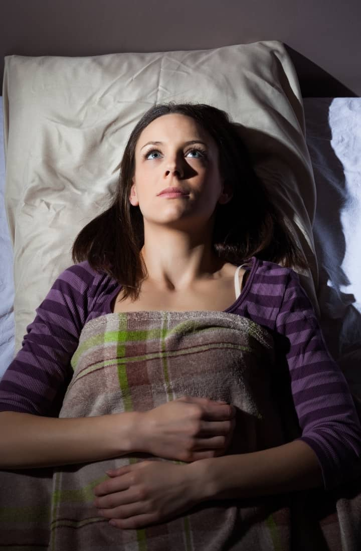 Overhead view of a woman wide awake in bed with insomnia, wearing a purple top and with her arms folded across her chest.