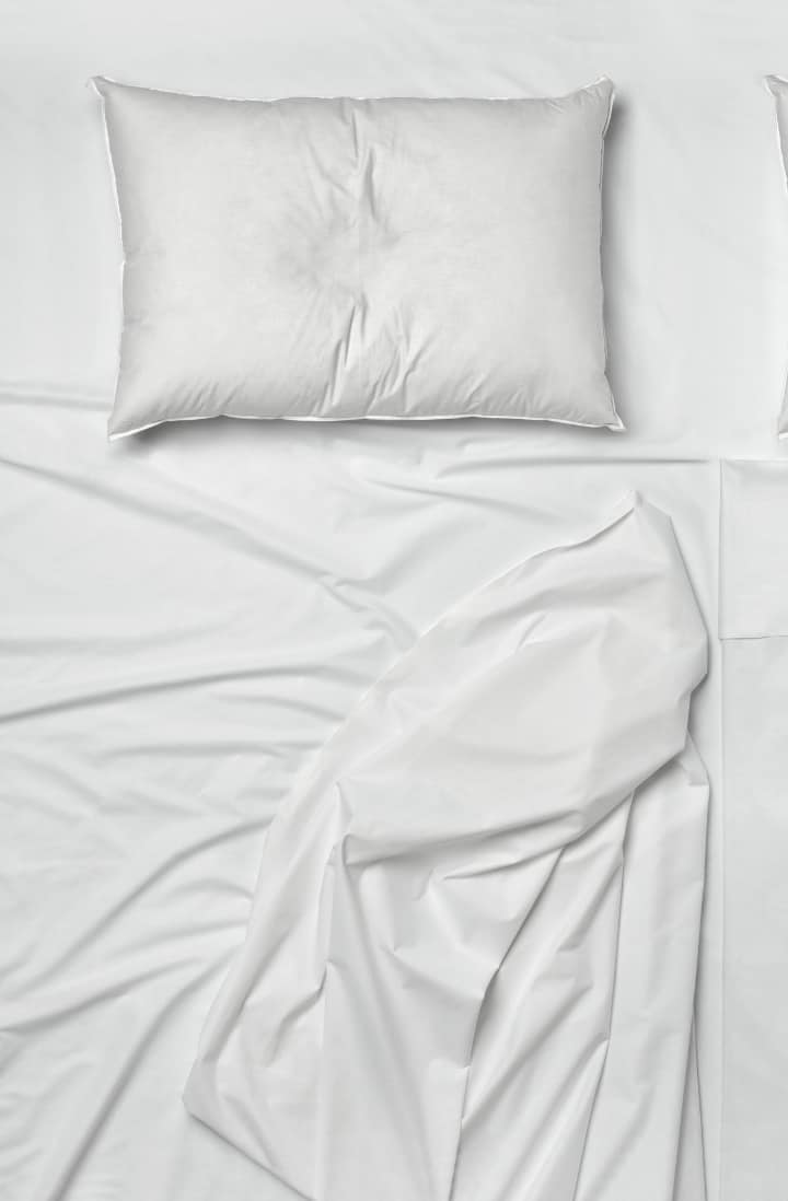 Overhead view of an empty bed, made with a white pillow and white sheets.