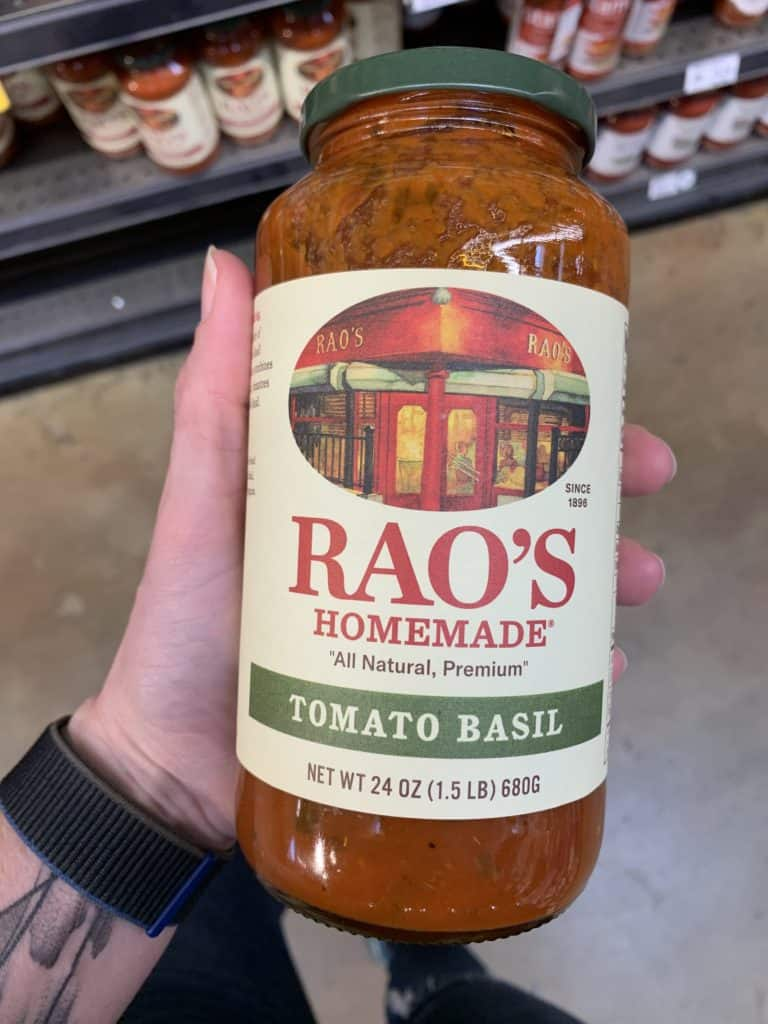 Close up image of a hand holding a large jar of Rao's pasta sauce.