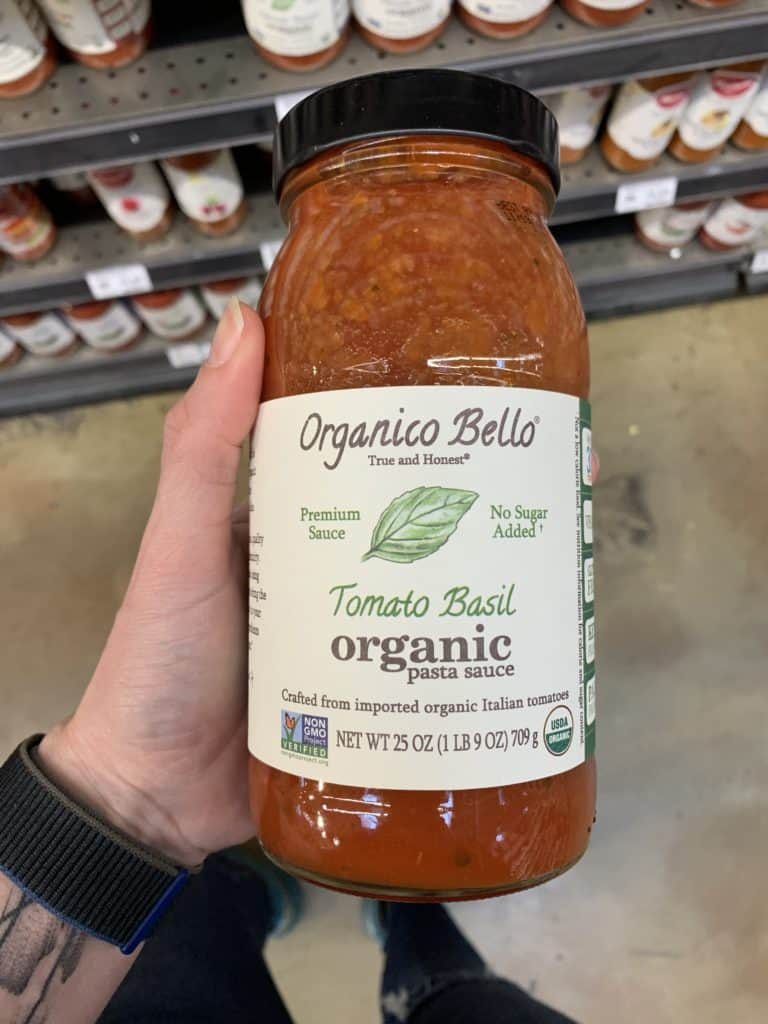 Close up image of a hand holding a large jar of Organico Bello pasta sauce.