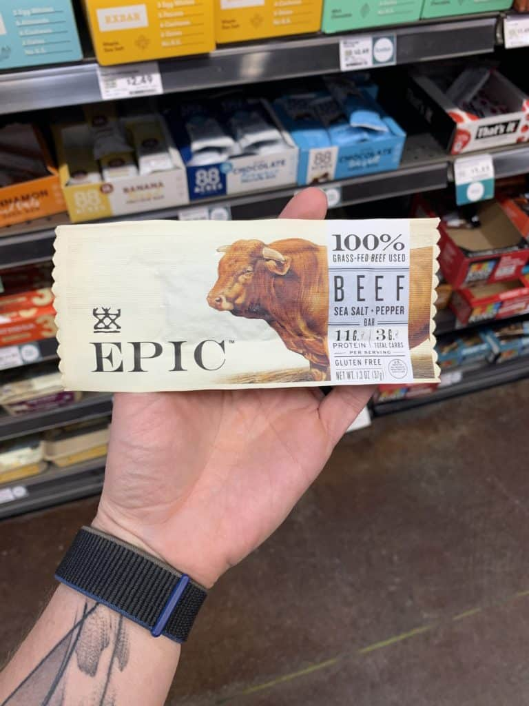 Close up image of a hand holding the Epic Protein Bar.