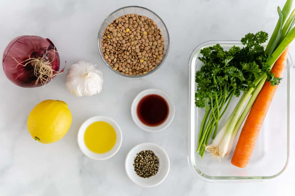 Overhead image of ingredients for the Cold Lentil Salad including Italian parsley, carrots, onion, lemon, and garlic.