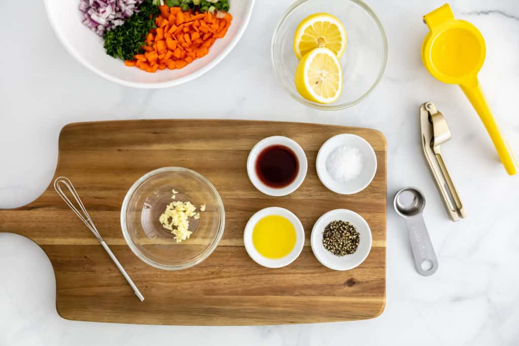 Overhead view of a cutting board with some of the ingredients for the Cold Lentil Salad including red wine vinegar, garlic, kosher salt and pepper.