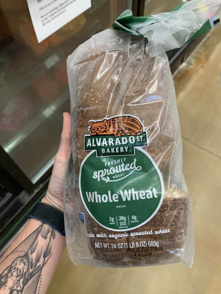Close up image of a hand holding a loaf of Alvarado St. Bakery Bread Bread with a clear and green label.
