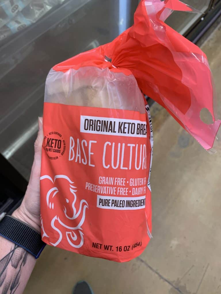Close up image of a hand holding a loaf of Base Culture Keto Bread Bread with a clear and red label.