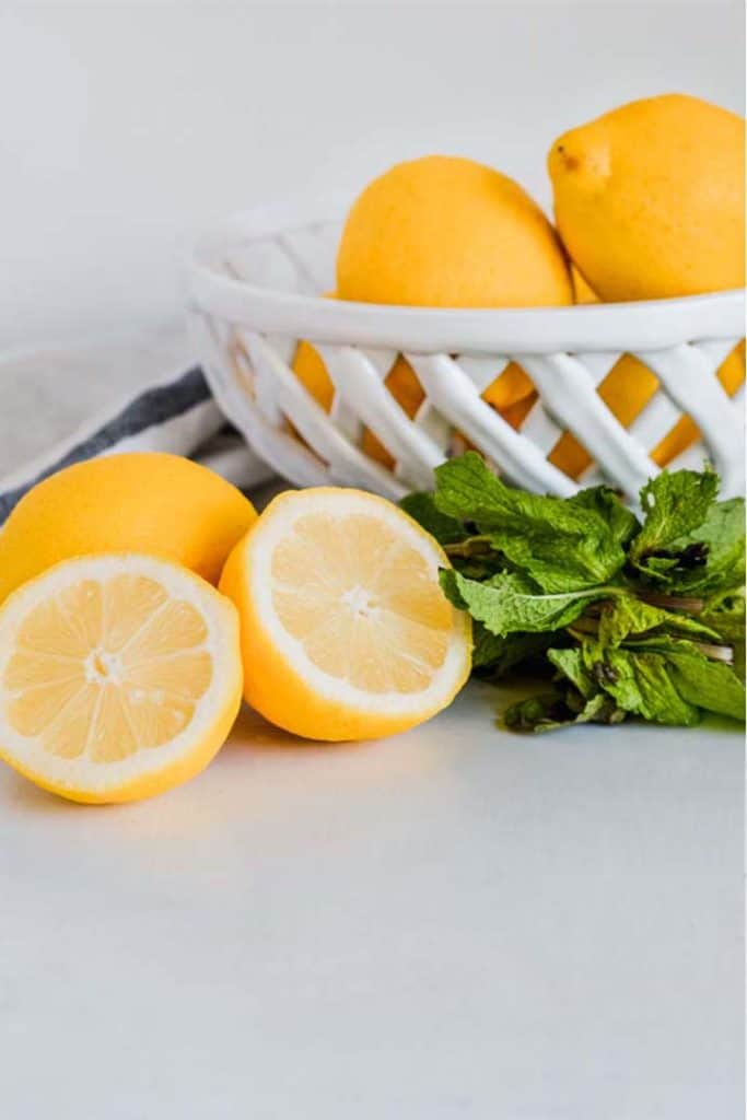 Close up side view of a basket of lemons, with a whole lemon, a lemon cut in half, and some mint leaves beside the basket.