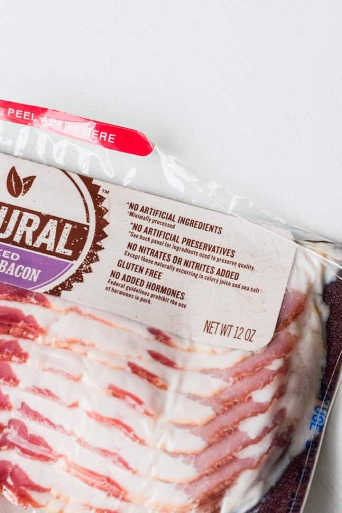 Overhead view of a package of bacon with the label showing no nitrates or nitrites, no hormones and no preservatives.