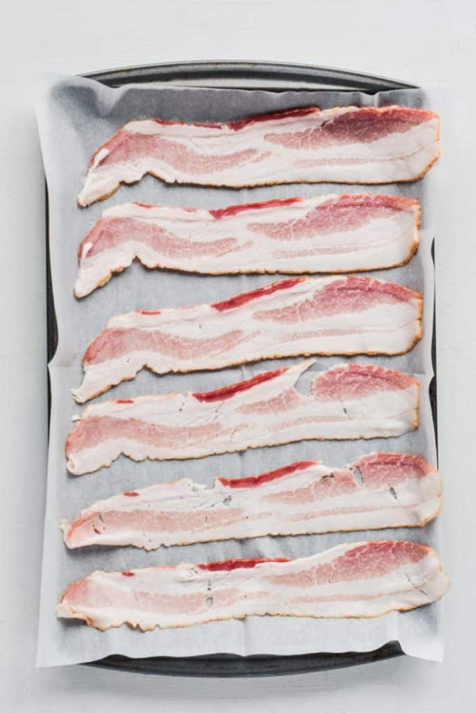 Overhead image of a parchment paper lined baking sheet with bacon placed on it ready to bake.