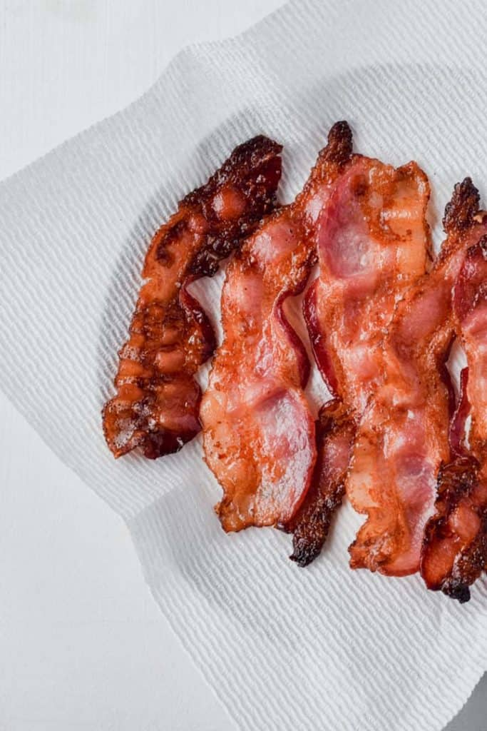 Overhead view of slices of bacon on paper towel draining.