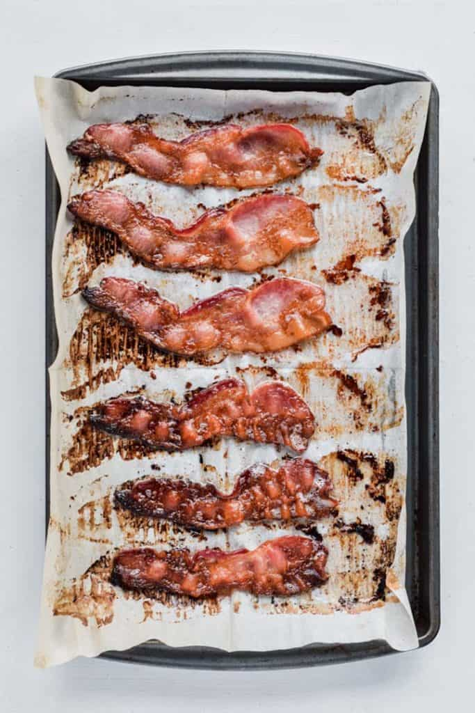Overhead image of a parchment paper lined baking sheet with bacon placed on it, baked in the oven.