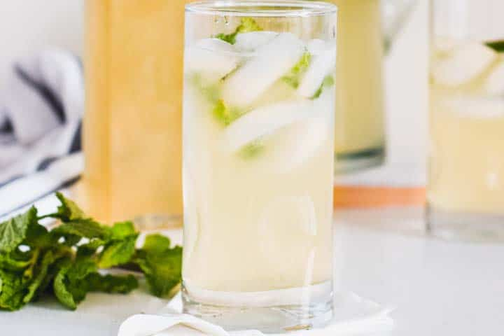 Close up side view of a glass of homemade mint lemonade, with ice and fresh mint in it, other glasses and mint are beside it.