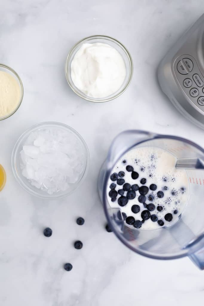 Overhead view of the blender with some of the ingredients added, including the almond milk and blueberries.